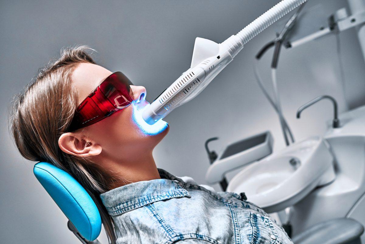 Kuva naispotilaasta ottamassa valotehostettua hampaiden valkaisua hammaslääkärin vastaanotolla.